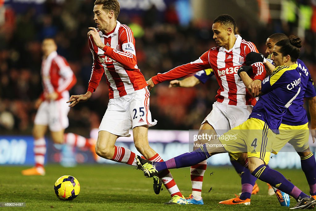 <a gi-track='captionPersonalityLinkClicked' href=/galleries/search?phrase=Peter+Crouch&family=editorial&specificpeople=210764 ng-click='$event.stopPropagation()'>Peter Crouch</a> (L) of Stoke City tries to evade the tackle of Chico Flores (R) of Swansea City during the Barclays Premier League match between Stoke City and Swansea City at the Britannia Stadium on February 12, 2014 in Stoke on Trent, England.