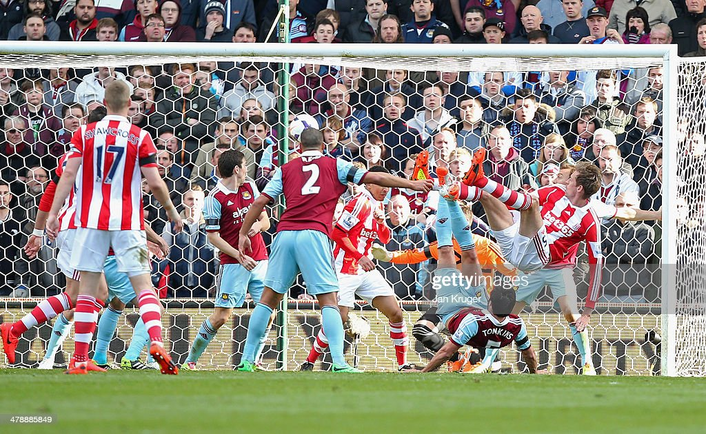 Peter Crouch of Stoke City's (R) shot deflects in to the goal off of Peter Odemwingie of Stoke City for their first as James Tomkins of West Ham United (5) challenges during the Barclays Premier League match between Stoke City and West Ham United at Britannia Stadium on March 15, 2014 in Stoke on Trent, England.