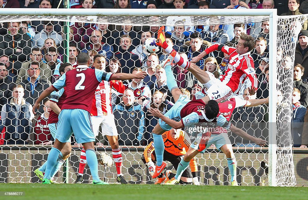 Peter Crouch of Stoke City's (25) shot deflects in to the goal off of Peter Odemwingie of Stoke City (3L) for their first as James Tomkins of West Ham United (5) challenges during the Barclays Premier League match between Stoke City and West Ham United at Britannia Stadium on March 15, 2014 in Stoke on Trent, England.