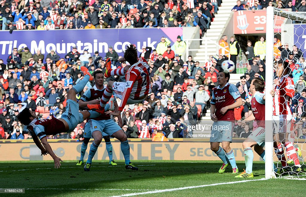 Peter Crouch of Stoke City's (25) shot deflects into the goal off of Peter Odemwingie of Stoke City for their first goal during the Barclays Premier League match between Stoke City and West Ham United at Britannia Stadium on March 15, 2014 in Stoke on Trent, England.