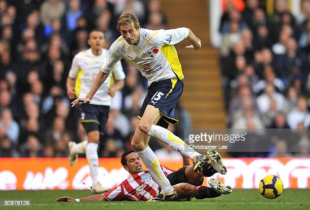 Peter Crouch of Tottenham Hotspur is tackled by Kieran Richardson of Sunderland during the Barclays Premier League match between Tottenham Hotspur...