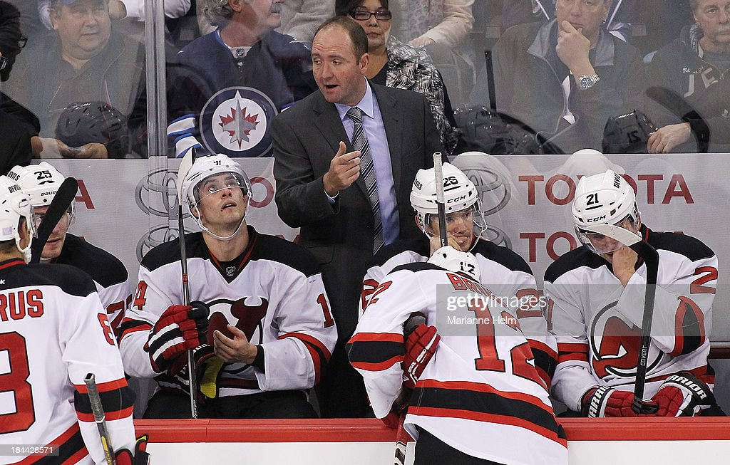 <a gi-track='captionPersonalityLinkClicked' href=/galleries/search?phrase=Peter+DeBoer&family=editorial&specificpeople=4235821 ng-click='$event.stopPropagation()'>Peter DeBoer</a>, head coach of the New Jersey Devils, talks to his team on the bench in third period action of an NHL game against the Winnipeg Jets at the MTS Centre on October 13, 2013 in Winnipeg, Manitoba, Canada.