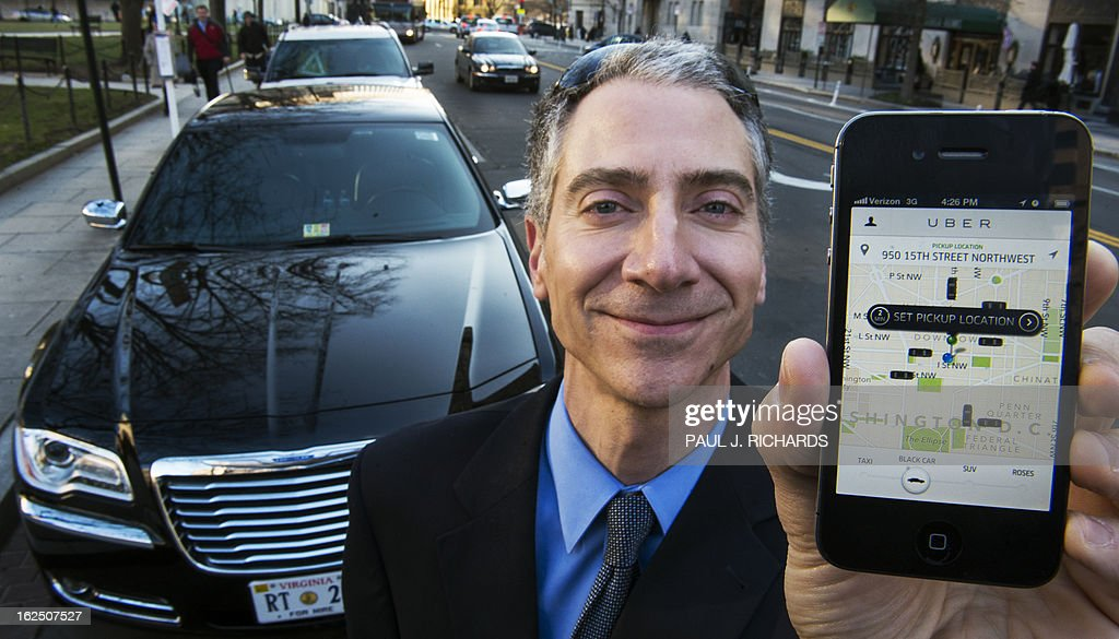 Peter Faris, CEO of Szabo Faris LLC Transportation Solutions, stands in front of one of his vehicles while holding a smart phone with an app that orders up his sedan service February 14, 2013 in Washington, DC. Faris, an independent driver who works with Uber, a technology firm which has created a mobile app which allows consumers to use their device to request a nearby taxi or limousine. Uber is among a number of apps which are being deployed in cities in the United States and worldwide. AFP Photo/Paul J. Richards
