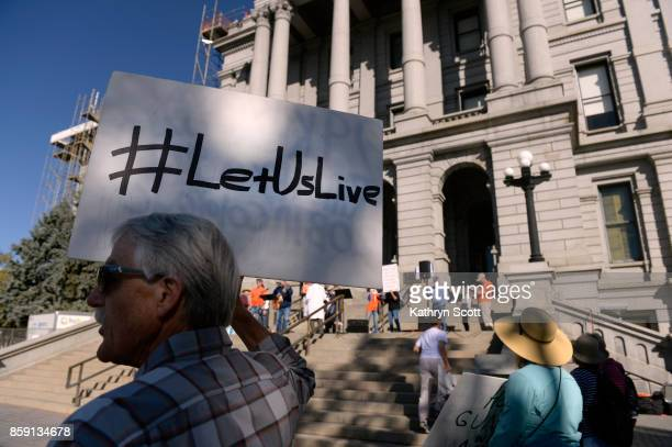 Peter Fogg stands with a small crowd on the west steps of the state capitol to join the Colorado Coalition Against Gun Violence for a rally on...