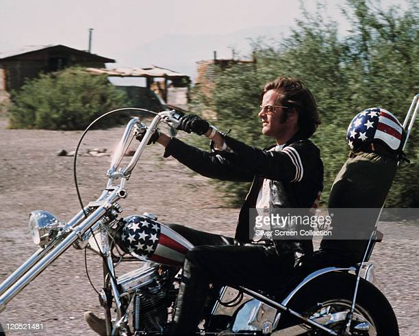 Peter Fonda US actor riding a chopper motorcycle with a starsandstripes helmet on the backrest of his seat in a publicity still issued for the film...