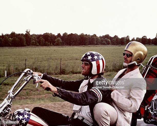 Peter Fonda wearng a starsandstripes helmet and Jack Nicholson wearing a gold American football helmet as they ride Fonda's chopper motorcycle in a...