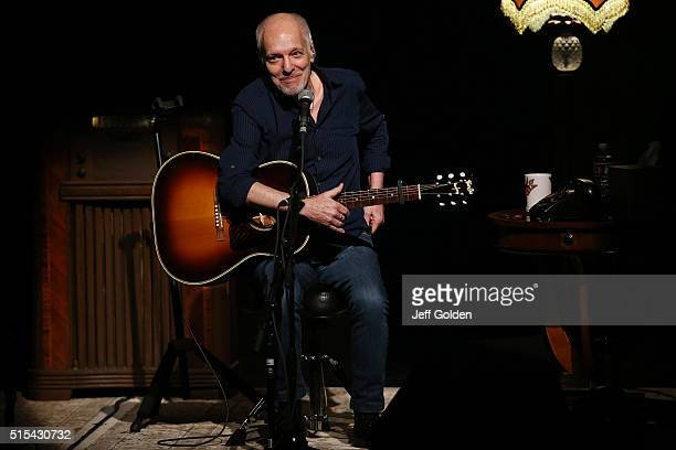 Peter Frampton smiles while removing his cell phone from his back pocket as he performs in support of his Raw An Acoustic Tour at Thousand Oaks Civic...