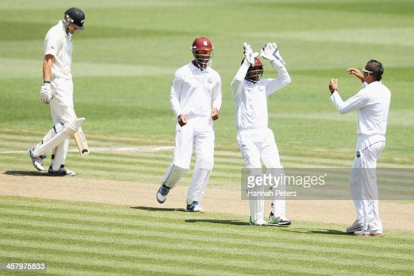 Peter Fulton of New Zealand walks off after being caught behind by Darren Sammy of the West Indies as Sunil Narine celebrates with Denesh Ramdin...