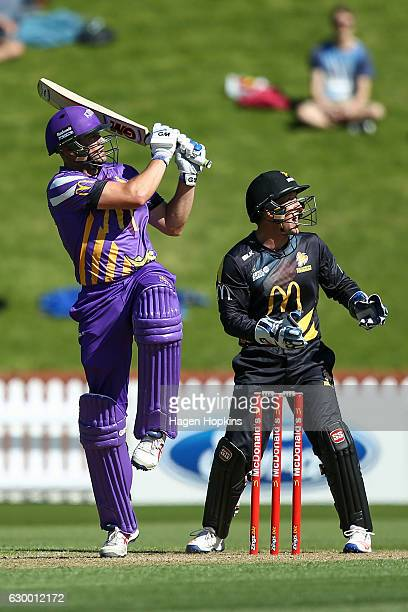 Peter Fulton of the Kings bats while Luke Ronchi of the Firebirds looks on during the McDonalds Super Smash T20 match between Wellington Firebirds...