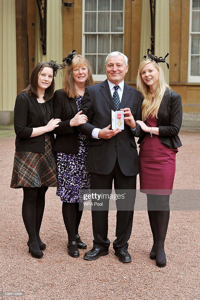 Peter Garrod, with wife Hazel and daughters Kirsty and Zoe (R) proudly holds his Officer of the British Empire (OBE), after it was presented to him by Queen Elizabeth II, at the Investiture ceremony at Buckingham Palace on November 16, 2012 in London, England.