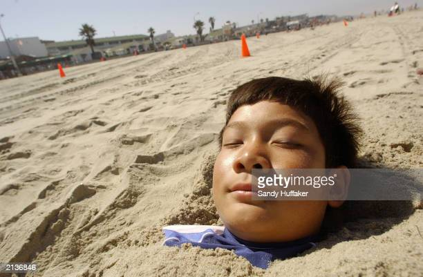 Peter Gidling soaks up the sun while being buried in the sand July 3 2003 at Pacific Beach in San Diego California Thousands of people are heading to...