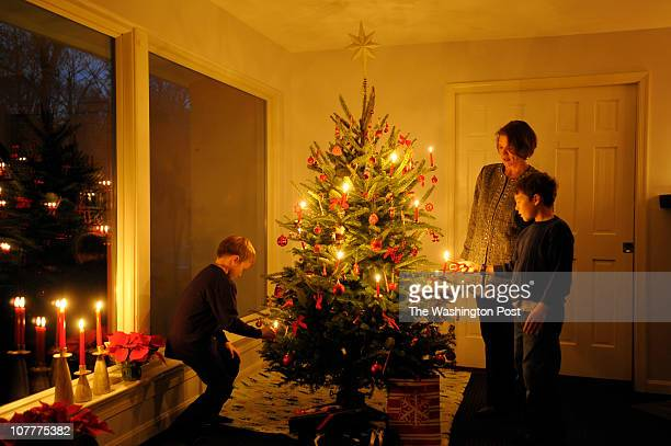Peter Greve left mother Louisa Greve center and son Nicholas Greve right help light the candles on their home Christmas tree The Greve family has...