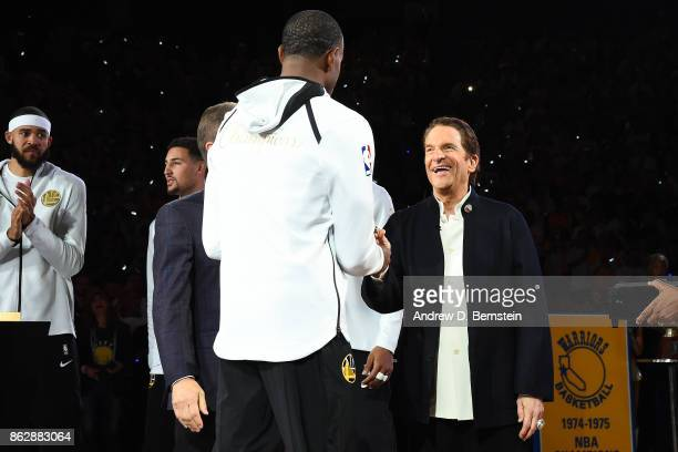 Peter Guber and Joe Lacob give Kevin Durant his championship ring during the Golden State Warriors ring ceremony before the game against the Houston...