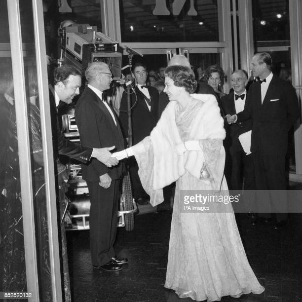 Peter Hall director of Britain's National Theatre bows to shake hand with the Queen as she arrives to open the theatre on London's South Bank At...