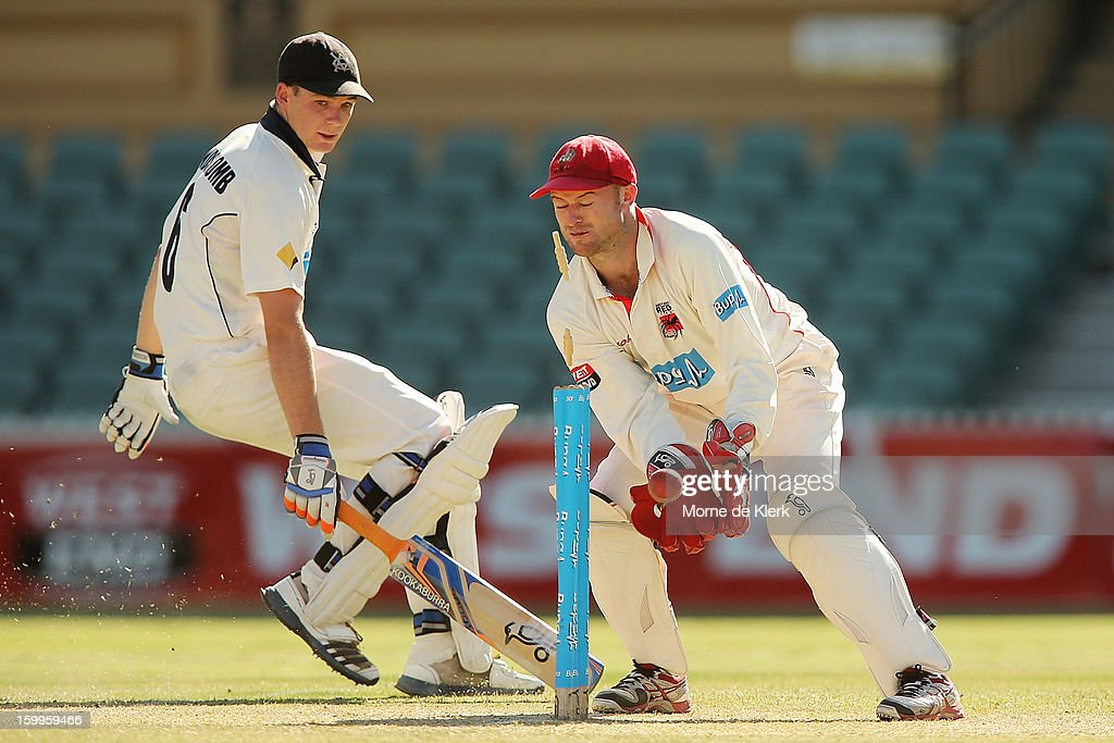 Peter Handscomb of the Bushrangers makes his ground as Tim Ludeman of the Redbacks keeps wicket during day one of the Sheffield Shield match between the South Australia Redbacks and the Victoria Bushrangers at Adelaide Oval on January 24, 2013 in Adelaide, Australia.