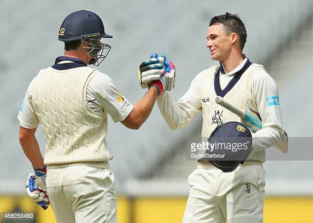 Peter Handscomb of Victoria is congratulated by Daniel Christian after he reached his century during day three of the Sheffield Shield match between...