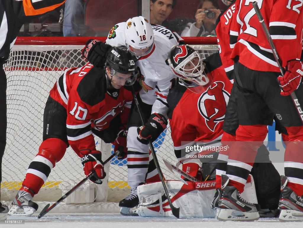 Peter Harrold #10 and Martin Brodeur #30 of the New Jersey Devils defend the net against Marcus Kruger #16 of the Chicago Blackhawks at the Prudential Center on March 27, 2012 in Newark, New Jersey.
