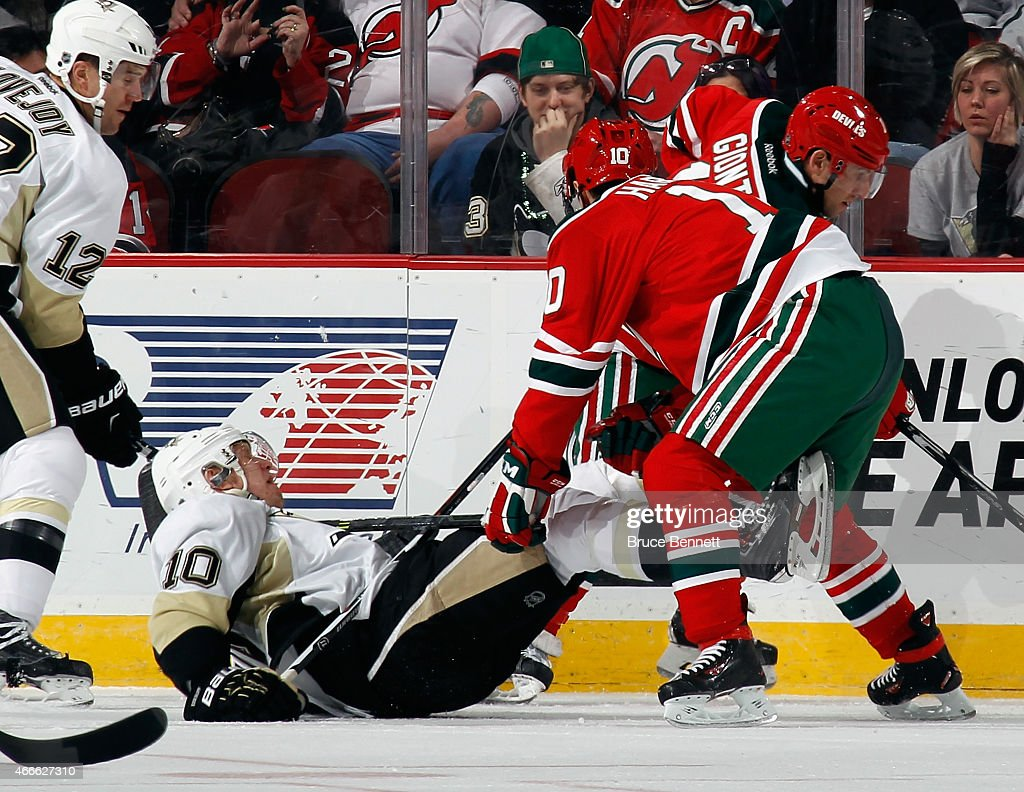 Peter Harrold of the New Jersey Devils hits Christian Ehrhoff of the Pittsburgh Penguins along the boards during the first period at the Prudential...