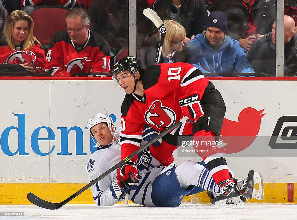 Peter Harrold #10 of the New Jersey Devils knocks David Clarkson #71 of the Toronto Maple Leafs to the ice during the third period at the Prudential Center on March 23, 2014 in Newark, New Jersey. The New Jersey Devils defeated the Toronto Maple Leafs 3-2.