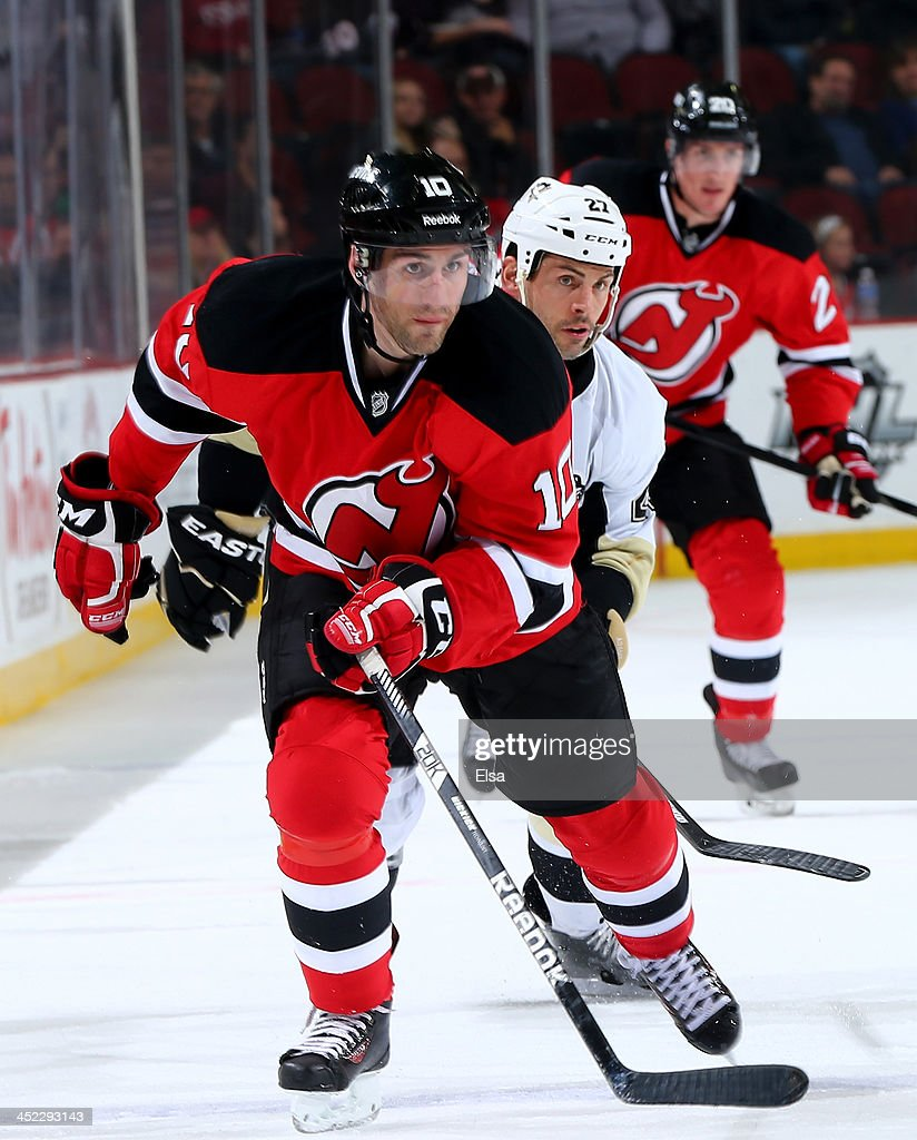 Peter Harrold of the New Jersey Devils skates ahead of Craig Adams of the Pittsburgh Penguins at Prudential Center on November 16 2013 in Newark New...