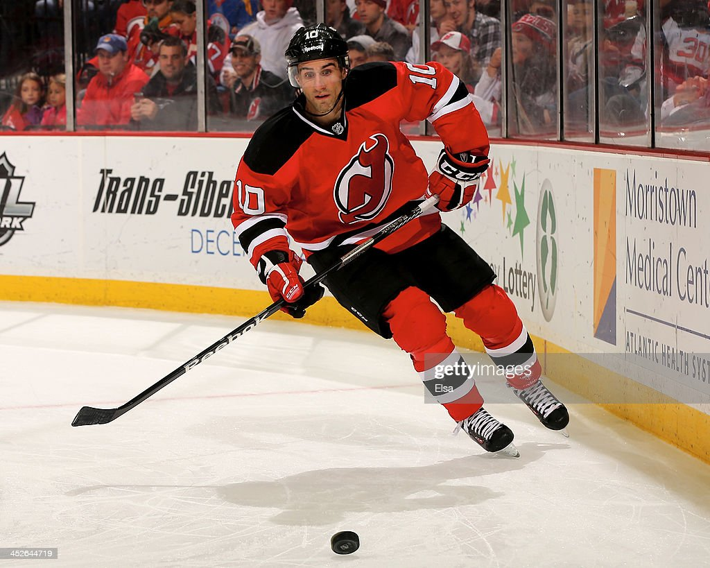 Peter Harrold of the New Jersey Devils takes the puck in the third period against the Carolina Hurricanes at Prudential Center on November 27 2013 in...