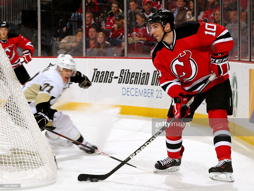 Peter Harrold of the New Jersey Devils tries to keep the puck from Evgeni Malkin of the Pittsburgh Penguins at Prudential Center on November 16 2013...