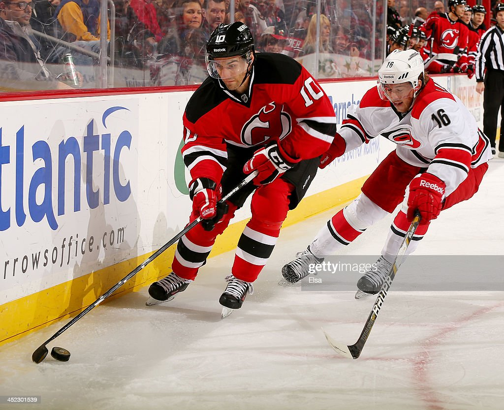 Peter Harrold of the New Jersey Devils tries to keep the puck from Elias Lindholm of the Carolina Hurricanes at Prudential Center on November 27 2013...