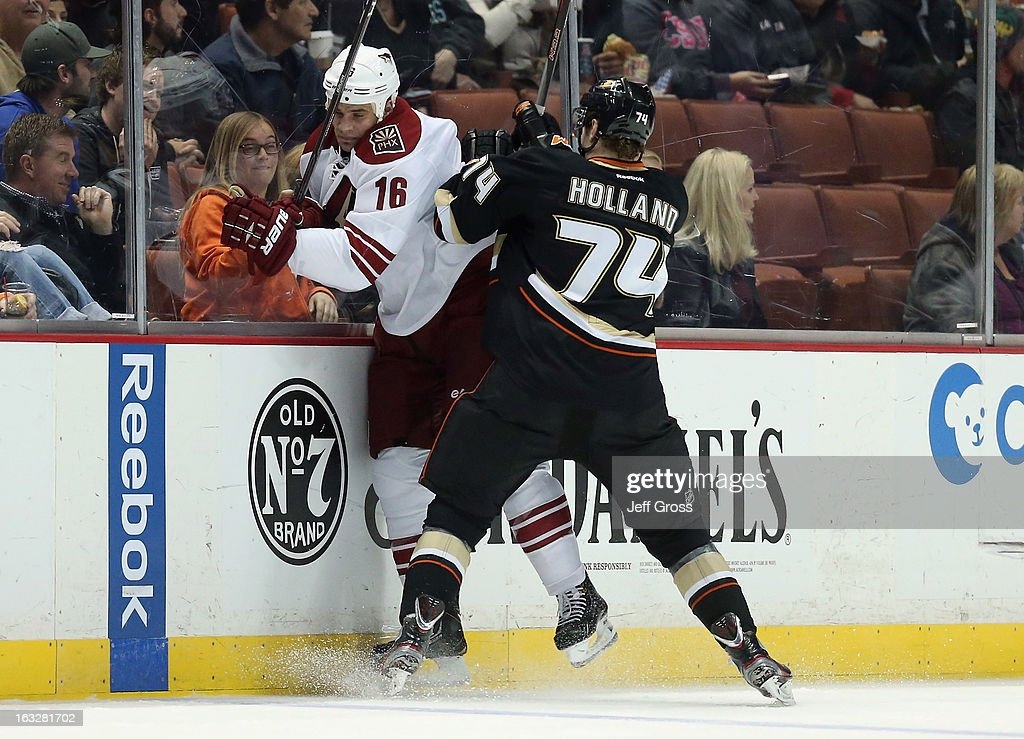 Peter Holland #74 of the Anaheim Ducks checks <a gi-track='captionPersonalityLinkClicked' href=/galleries/search?phrase=Rostislav+Klesla&family=editorial&specificpeople=207079 ng-click='$event.stopPropagation()'>Rostislav Klesla</a> #16 of the Phoenix Coyotes into the boards in the first period at Honda Center on March 6, 2013 in Anaheim, California. The Ducks defeated the Coyotes 2-0.