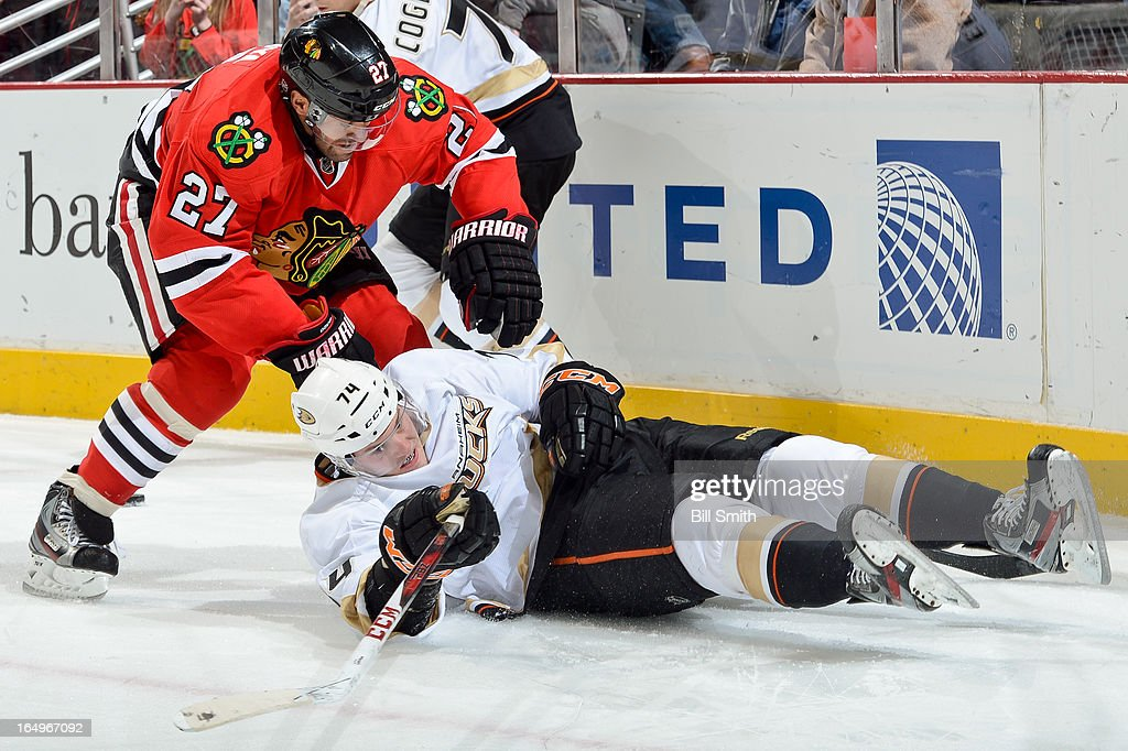 Peter Holland #74 of the Anaheim Ducks falls to the ice as <a gi-track='captionPersonalityLinkClicked' href=/galleries/search?phrase=Johnny+Oduya&family=editorial&specificpeople=3944055 ng-click='$event.stopPropagation()'>Johnny Oduya</a> #27 of the Chicago Blackhawks skates up behind during the NHL game on March 29, 2013 at the United Center in Chicago, Illinois.