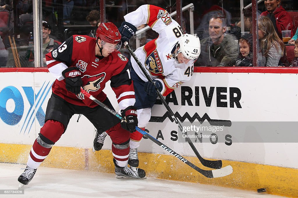 Peter Holland #13 of the Arizona Coyotes and Michael Sgarbossa #48 of the Florida Panthers battle for a loose puck during the second period of the NHL game at Gila River Arena on January 23, 2017 in Glendale, Arizona.
