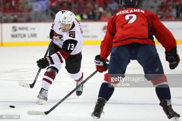Peter Holland of the Arizona Coyotes shoots in front of Matt Niskanen of the Washington Capitals during the first period at Verizon Center on March...