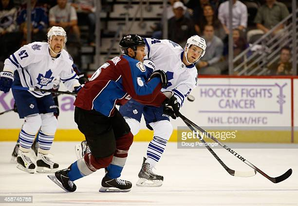 Peter Holland of the Toronto Maple Leafs controls the puck against Erik Johnson of the Colorado Avalanche at Pepsi Center on November 6 2014 in...