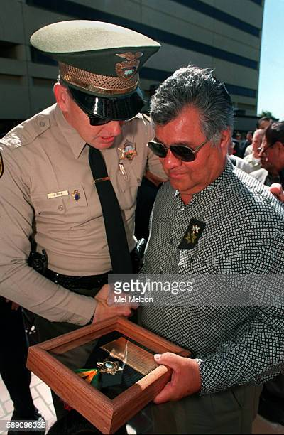 Peter John Aguirre Sr right father of slain ventura county deputy Peter John Aguirre Jr looks at medal given in memory of his son while receiving a...