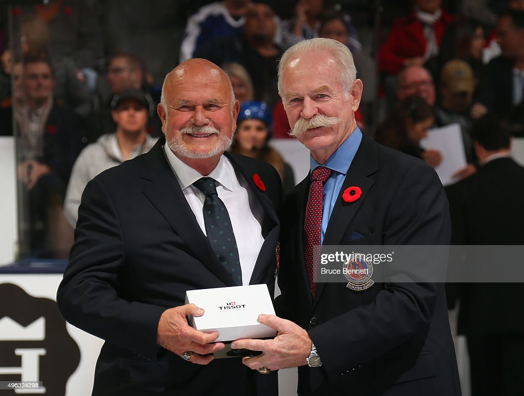 Peter Karmanos Jr receives his Hockey Hall of Fame blazer from the Chairman of the Hockey Hall of Fame Lanny McDonald prior to the Legends Classic...