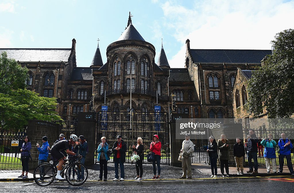 Peter Kennaugh of Isle of Man cycles past Glasgow University in the Men's Road Race during day eleven of the Glasgow 2014 Commonwealth Games on...