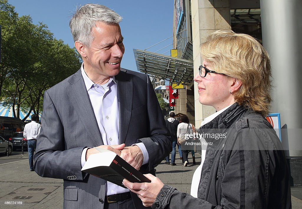 Peter Kloeppel (RTL chief-editor) gives a book to a pedestrian during the world day of the book on April 23, 2014 in Cologne, Germany. World book day is a yearly event on April 23rd, organized by UNESCO to promote reading, publishing and copyright.