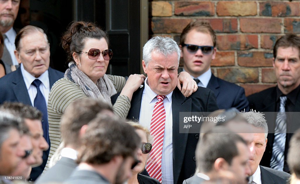 Peter Lane (centre R), father of Australian baseball player Chris Lane, who was killed in the small Oklahoma town of Duncan in the US, is surrounded by friends and family outside St Therese's Parish at Chris's funeral in Melbourne on August 28, 2013. Chris Lane, 22, was in the US on a baseball scholarship and was jogging in Duncan when he was shot in the back and left to die on the side of the road on August 16. Two teenagers, aged 15 and 16, have been accused of shooting Lane, while a third, aged 17, was charged with use of a vehicle in the discharge of a weapon and acting as an accessory after the fact. AFP PHOTO / Mal Fairclough