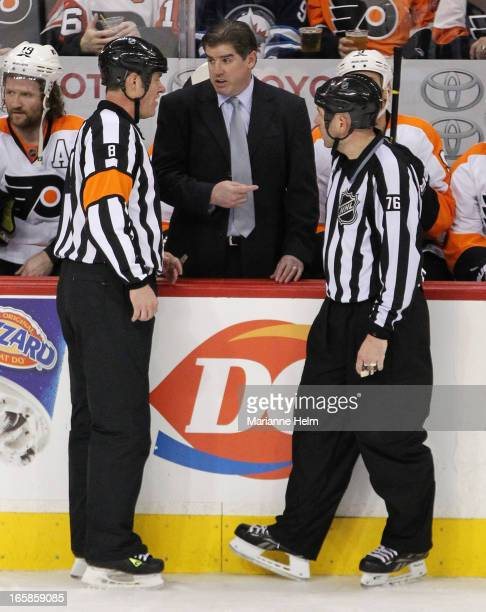 Peter Laviolette head coach of the Philadelphia Flyers speaks with referee Dave Jackson and linesman Michael Cormier during third period in a game...