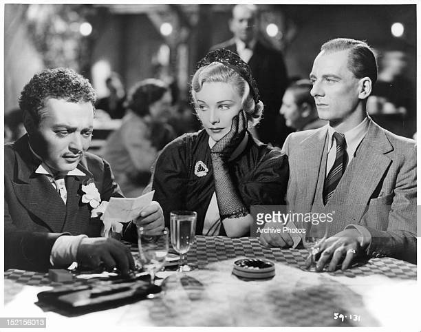 Peter Lorre reads a note while Madeleine Carroll and John Gielgud listen while they all sit at a table in a scene from the film 'Secret Agent' 1936