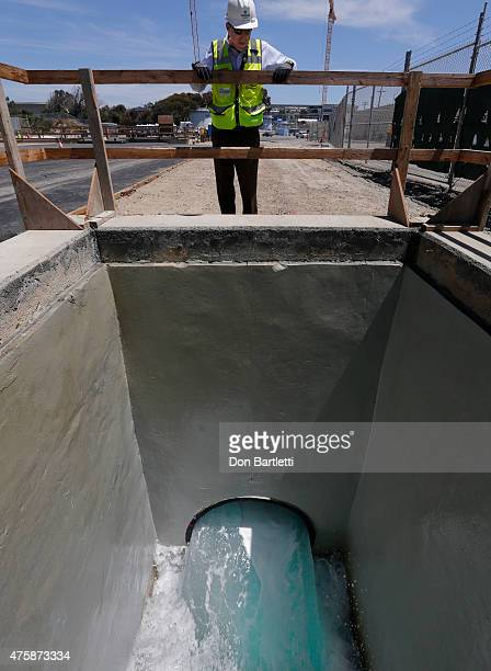 Peter MacLaggan Senior VP for Project Development at Poseidon Water looks down at a test flow of brine water at the Poseidon Water desalination plant...