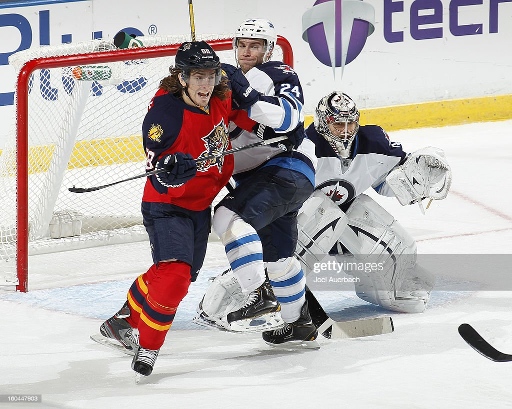 Peter Mueller #88 of the Florida Panthers battles for position in front of goaltender Ondrej Pavelec #31 with Grant Clitsome #24 of the Winnipeg Jets at the BB&T Center on January 31, 2013 in Sunrise, Florida. The Panthers defeated the Jets 6-3.