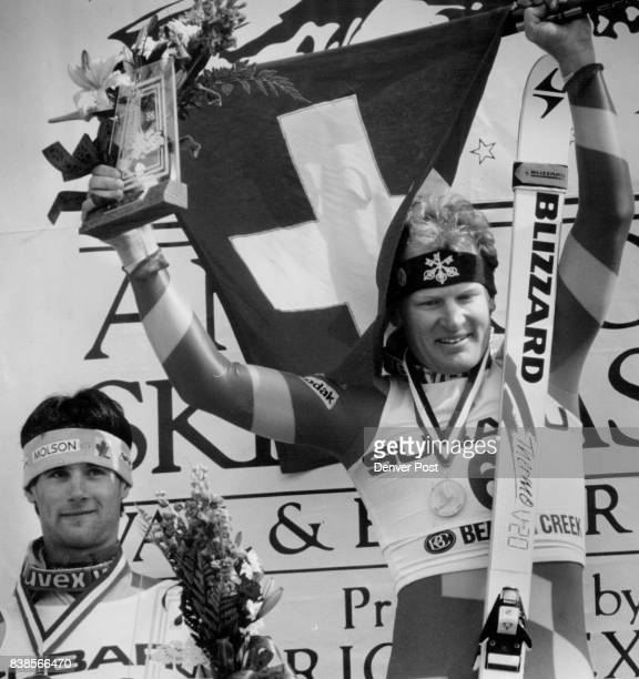 Peter Mueller waves the Swiss flag after he won the downhill at Beaver Creek Sat Looking on his Donald Stevens of Canada who came from the 42nd...