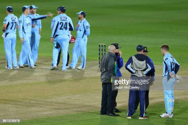Peter Nevill of NSW and Peter Handscomb of Victoria talk to umpires Phillip Gillespie John Ward and match referee Daryl Harper during the JLT One Day...