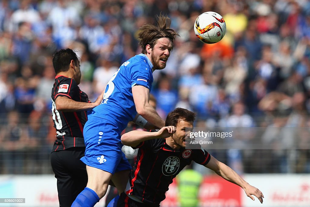 Peter Niemeyer (C) of Darmstadt jumps for a header with Szabolcs Huszti (front) and Marco Fabian of Frankfurt during the Bundesliga match between SV Darmstadt 98 and Eintracht Frankfurt at Merck-Stadion am Boellenfalltor on April 30, 2016 in Darmstadt, Hesse.