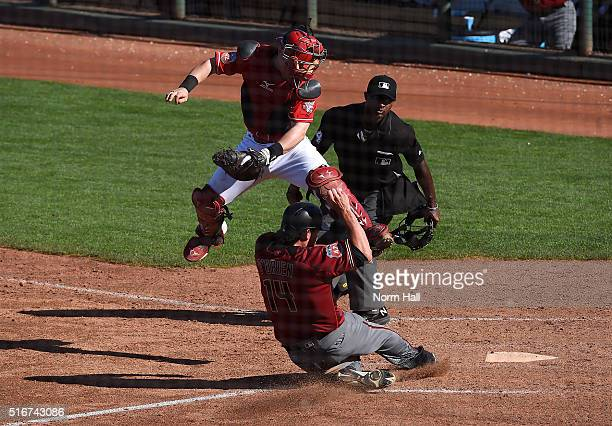 Peter O'Brien of the Arizona Diamondbacks slides safely into home plate under the tag of a leaping Tucker Barnhart of the Cincinnati Reds during the...
