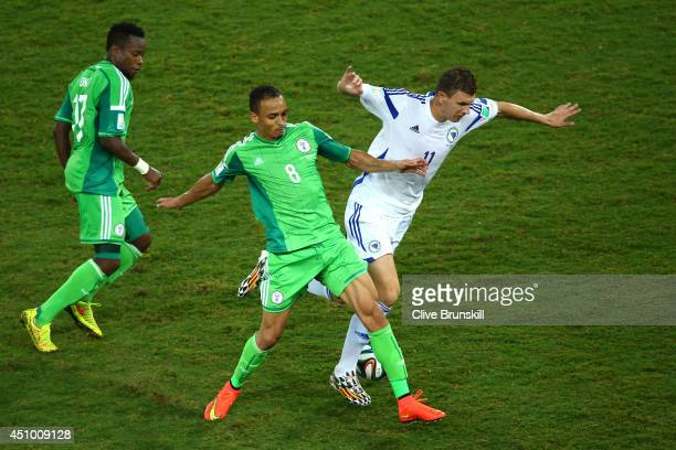Peter Odemwingie of Nigeria challenges Edin Dzeko of Bosnia and Herzegovina during the 2014 FIFA World Cup Group F match between Nigeria and...