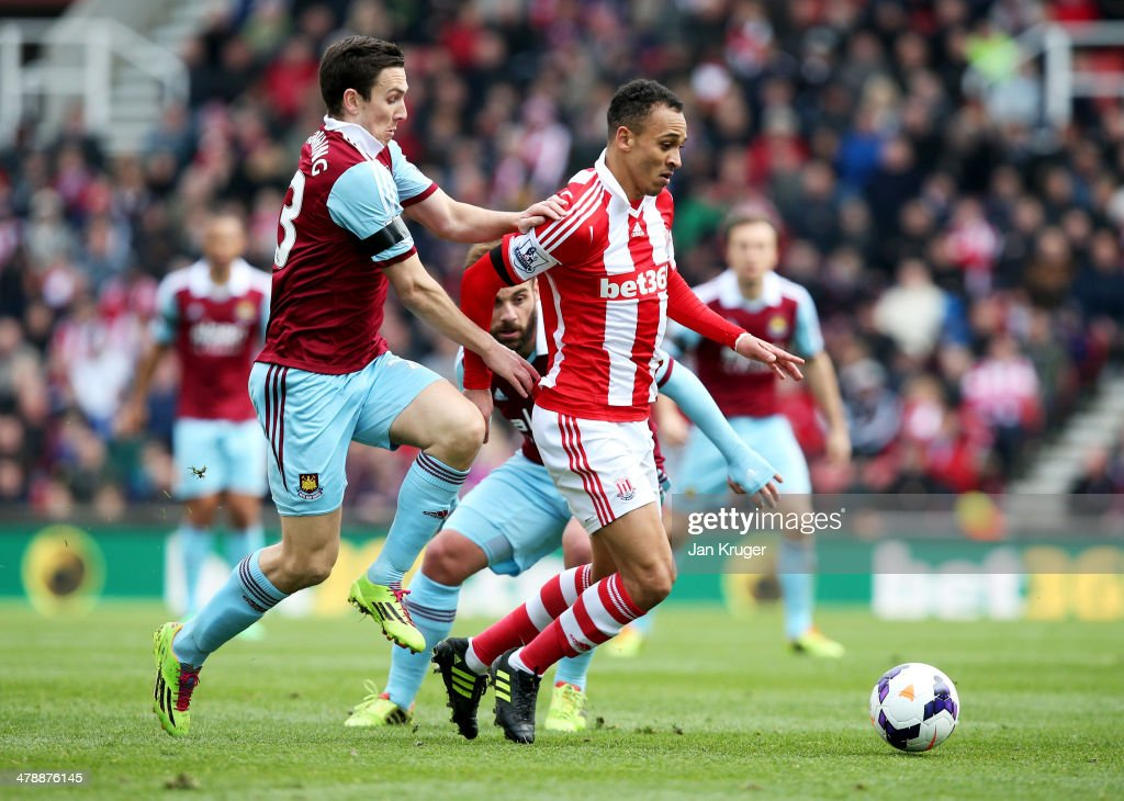 Peter Odemwingie of Stoke City holds off Stewart Downing of West Ham United during the Barclays Premier League match between Stoke City and West Ham United at Britannia Stadium on March 15, 2014 in Stoke on Trent, England.