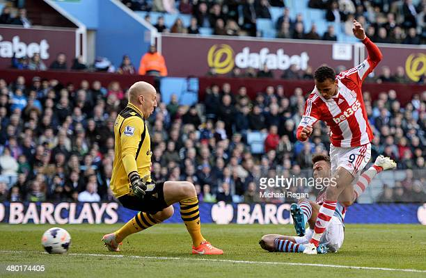 Peter Odemwingie of Stoke shoots past goalkeeper Brad Guzan of Aston Villa to score a goal to level the scores at 11 during the Barclays Premier...