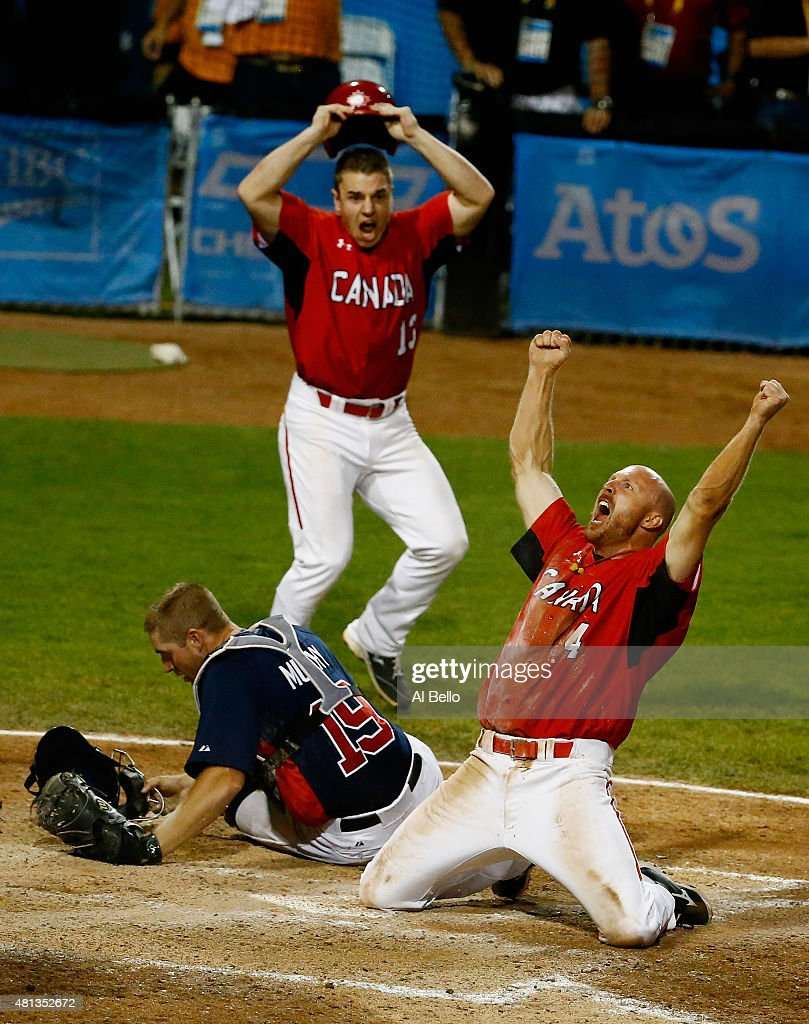 Peter Orr of Canada celebrates scoring the winning run in the tenth inning as Thomas Murphy of the USA and Tyler O'Neill of Canada looks after their...