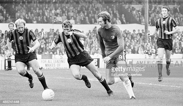 Peter Osgood of Chelsea races past Tony Book and David Connor of Manchester City during their Division One football match at Stamford Bridge in...